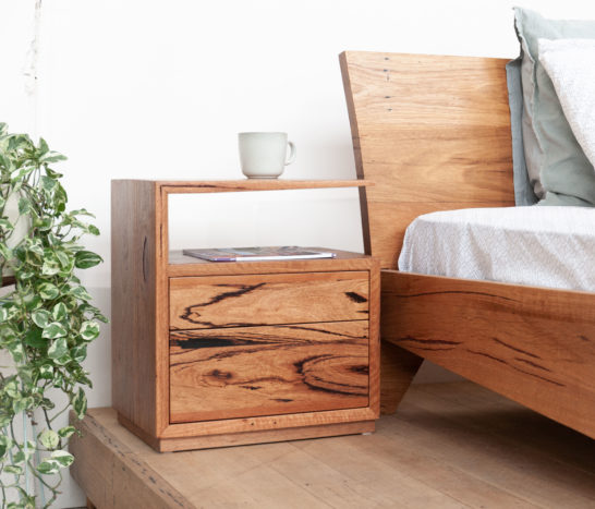 timber bedside table with queen bed and plant