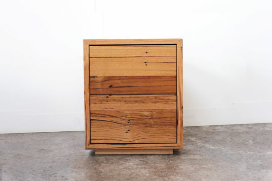 Timber bedside table against white wall