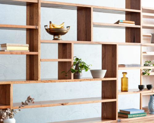 timber bookshelf with plants and glassware
